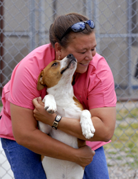 Brenda gets a dog kiss from Quincy, a beagle cross.