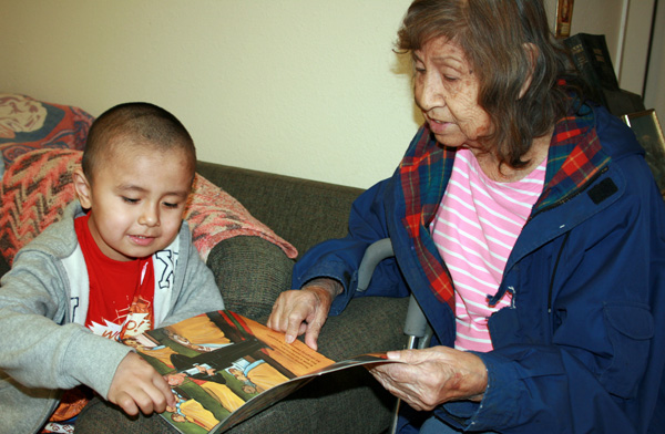 Native American child with books reading with his grandmother