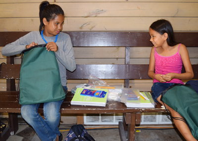 A photo of two students, Eliza and Evoni, receiving school supplies
