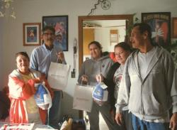 Native American people receiving items for Thanksgiving dinner.