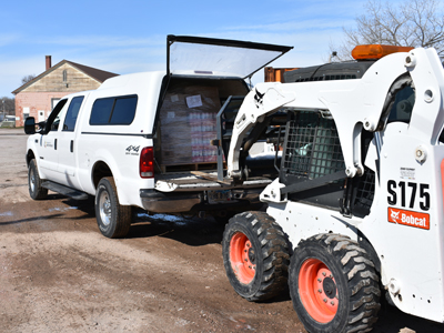 Photo of a Bobcat unloading a pallet of supplies