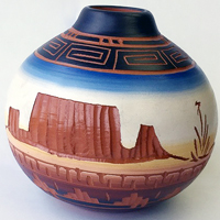 This authentic Native American Navajo pottery is artfully hand-etched and painted. The artist carves the design by hand before the firing process, and then adds hand-painted detail to the piece to create the unique look. It depicts the monuments near the Four Corners area of the Navajo Nation and measures 4.75